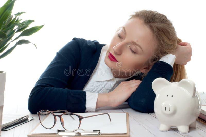 Overwerkte en vermoeide jonge vrouwenslaap op bureau op kantoor royalty-vrije stock fotografie