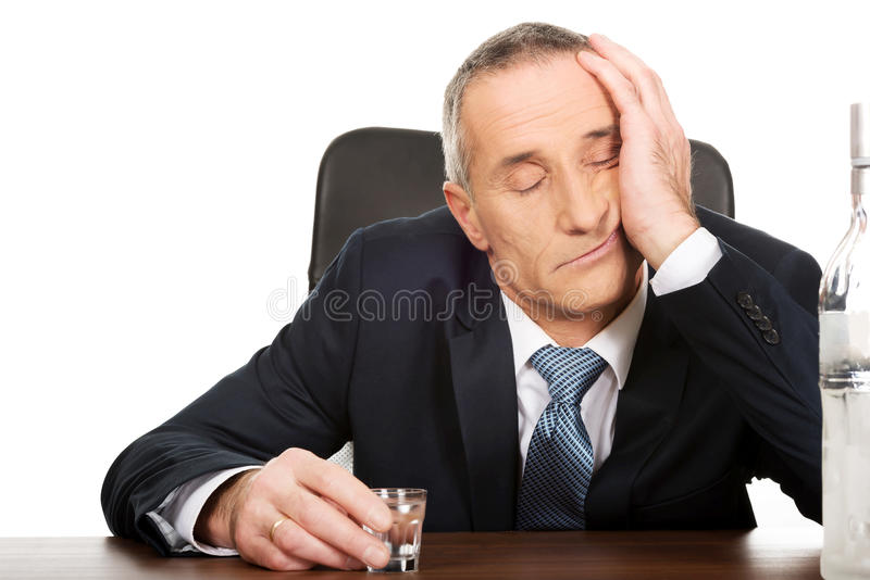Overwerkte mens het drinken wodka in bureau stock fotografie