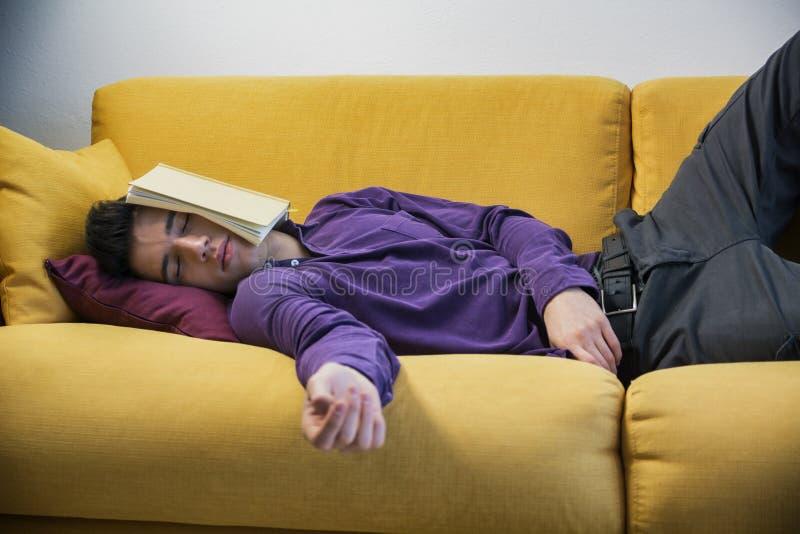 Overwerkte, vermoeide jonge mens die thuis slapen stock afbeeldingen