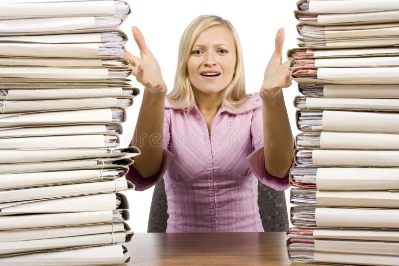 Overwerkte vrouw bij het bureau stock afbeeldingen