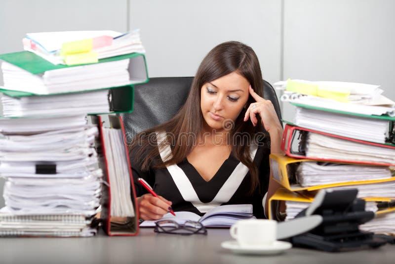 Overwerkte vrouw in bureau stock foto's