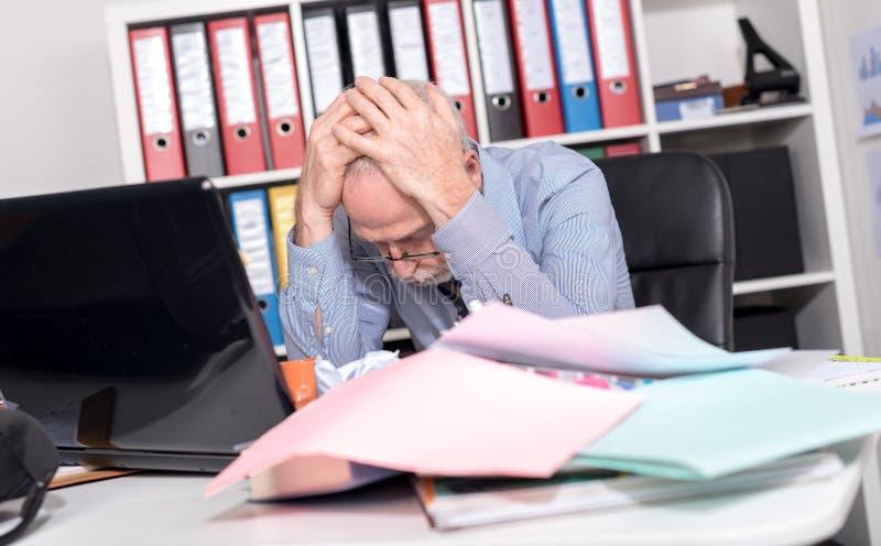 Overwerkte zakenmanzitting bij een slordig bureau stock foto's