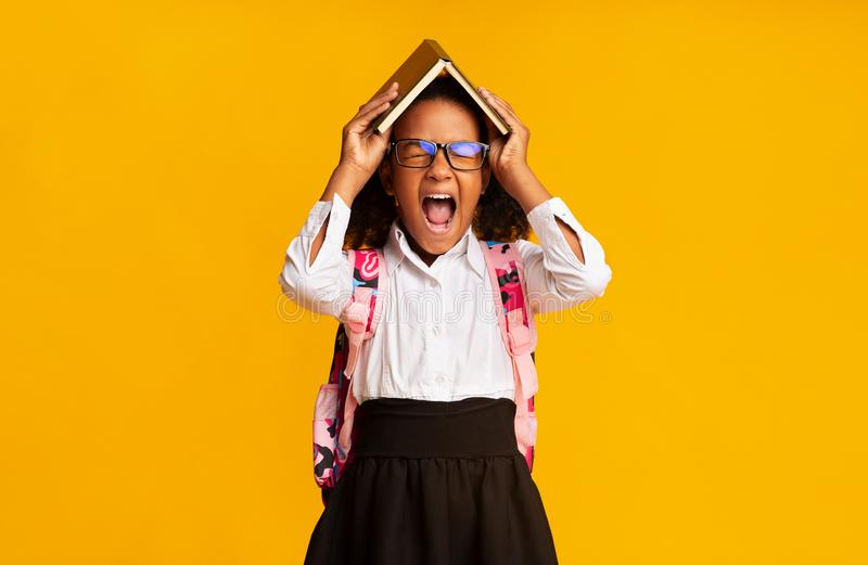 Overwhelmed Black School Student Girl Shouting Covering Head With Book. School Overwork. Little Black Schoolgirl Shouting Covering Head With Book On Yellow stock image