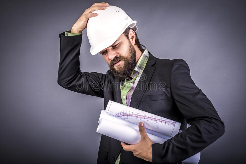 Overwhelmed businessman with hardhat stock image