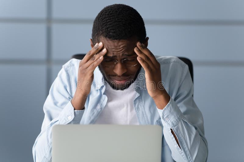 Overwhelmed exhausted young worker suffering from strong head pain. royalty free stock images