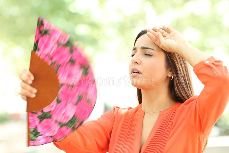 Overwhelmed girl suffering heat stroke in the street. Overwhelmed girl suffering heat stroke fanning in the street in summer royalty free stock photos