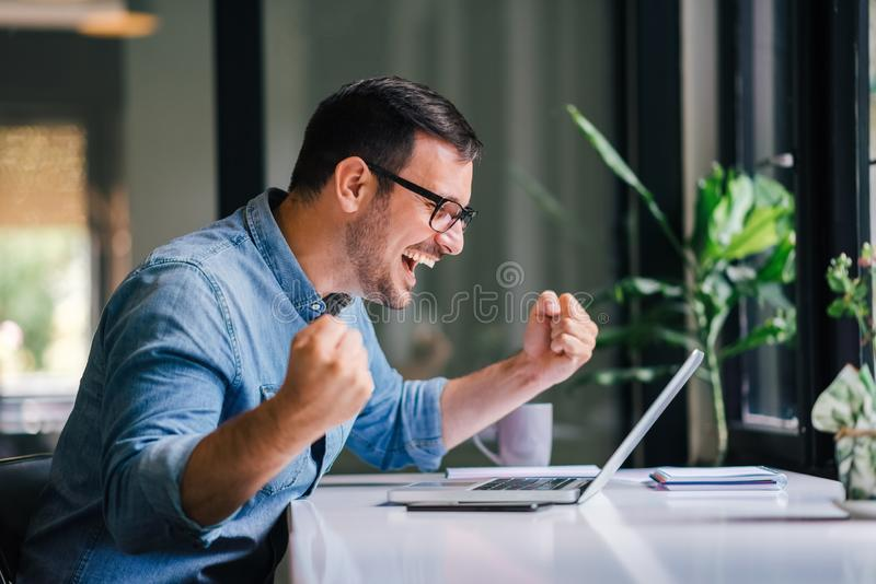 Overwhelmed by success young cheerful adult casual businessman or entrepreneur smiling and vividly celebrating with raised hands royalty free stock photos