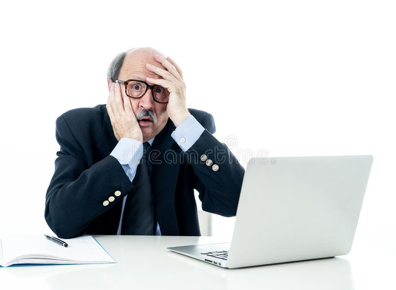 Overwhelmed and tired old businessman working with laptop feeling angry at office stock photography