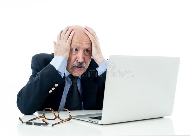 Overwhelmed and tired old businessman working with laptop feeling angry at office stock images