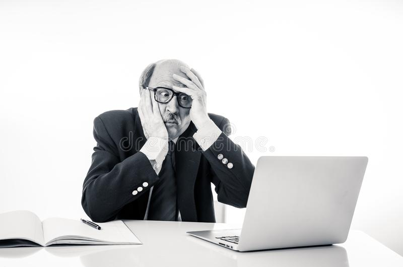 Overwhelmed and tired old businessman working with laptop feeling angry at office royalty free stock photos