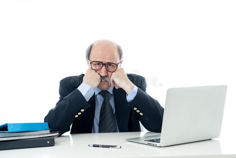 Overwhelmed and tired old businessman working with laptop feeling angry at office stock photo