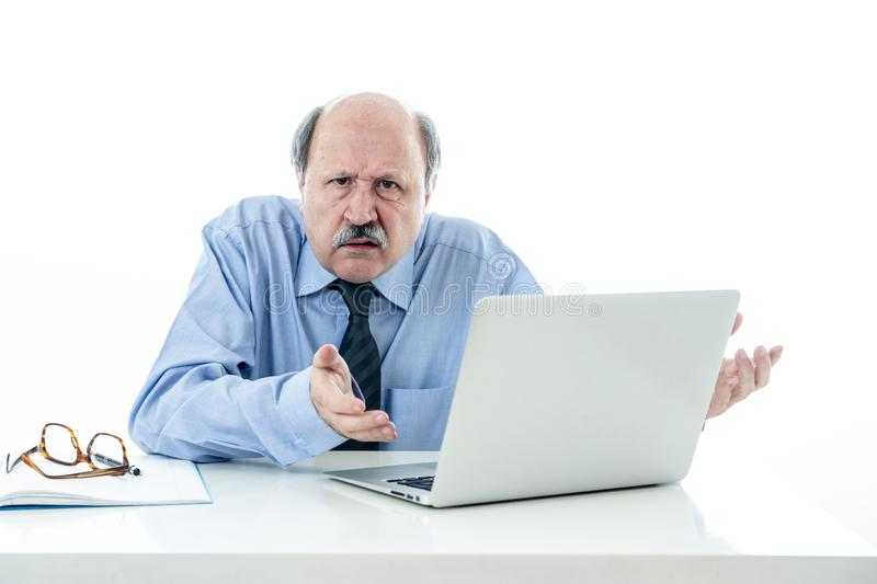 Overwhelmed and tired old businessman working with laptop feeling angry at office royalty free stock image