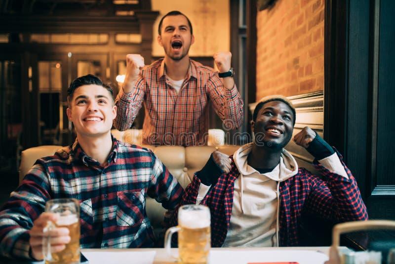 overwinning Groep jonge mooie vrienden die op TV letten en voor hun team toejuichen terwijl het rusten in bar royalty-vrije stock fotografie