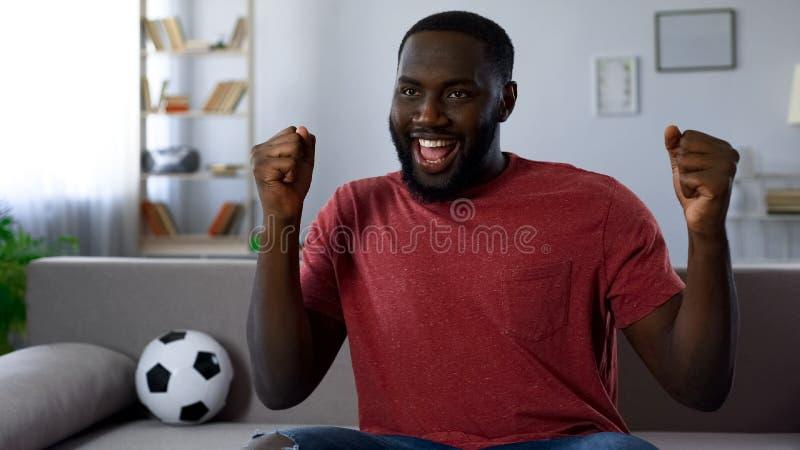 Overwinning van favoriet voetbalteam, Afrikaans-Amerikaanse mens die victoriously dansen royalty-vrije stock afbeeldingen