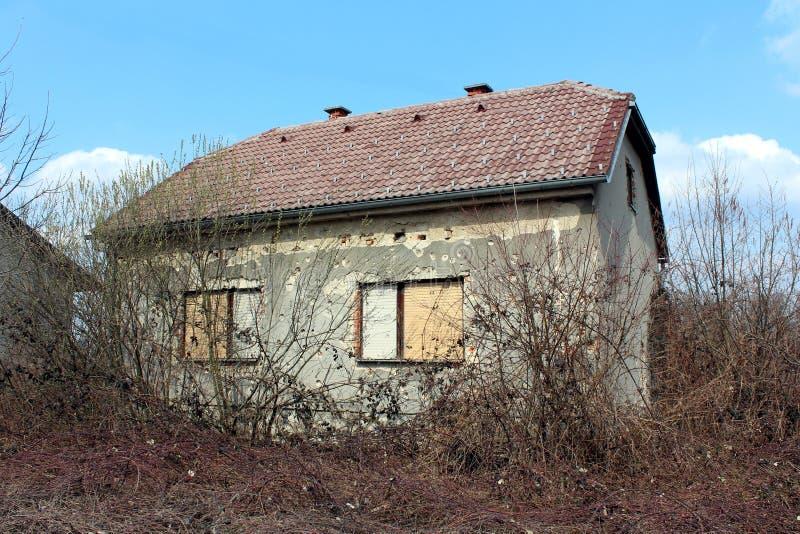 Overwoekerd familiehuis in de voorsteden die door granaatscherven tijdens oorlog wordt beschadigd royalty-vrije stock foto