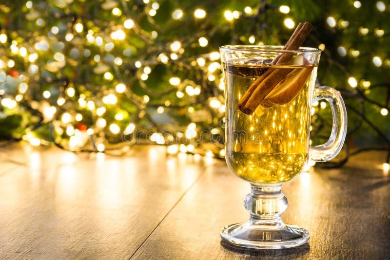 overwogen cider in glas, ornamenten en Kerstmislicht op hout royalty-vrije stock foto's