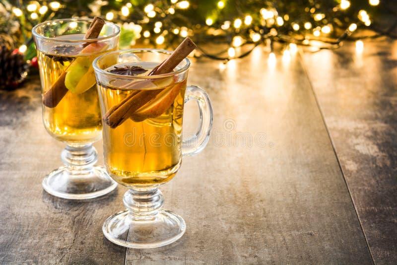overwogen cider in glas, ornamenten en Kerstmislicht op hout royalty-vrije stock foto