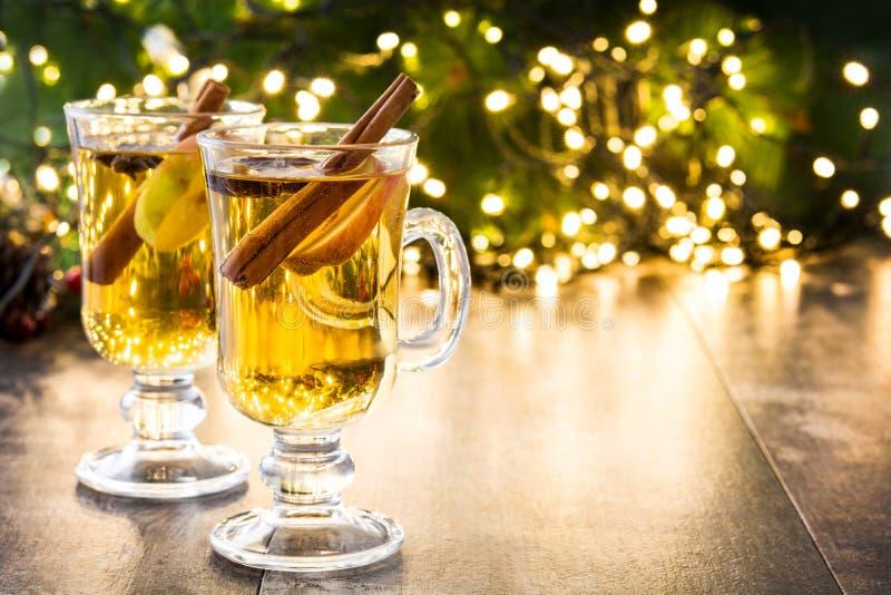 overwogen cider in glas, ornamenten en Kerstmislicht op hout stock afbeeldingen