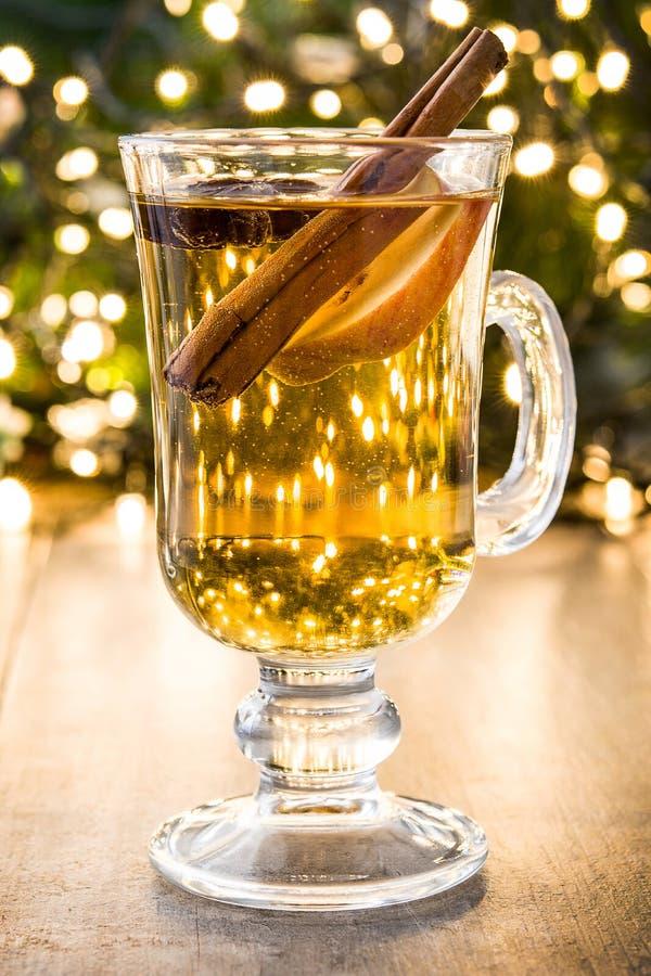 overwogen cider in glas, ornamenten en Kerstmislicht op hout stock afbeelding