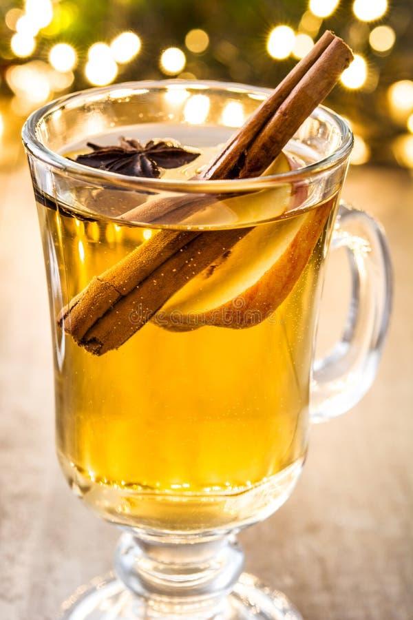 overwogen cider in glas, ornamenten en Kerstmislicht op hout stock fotografie