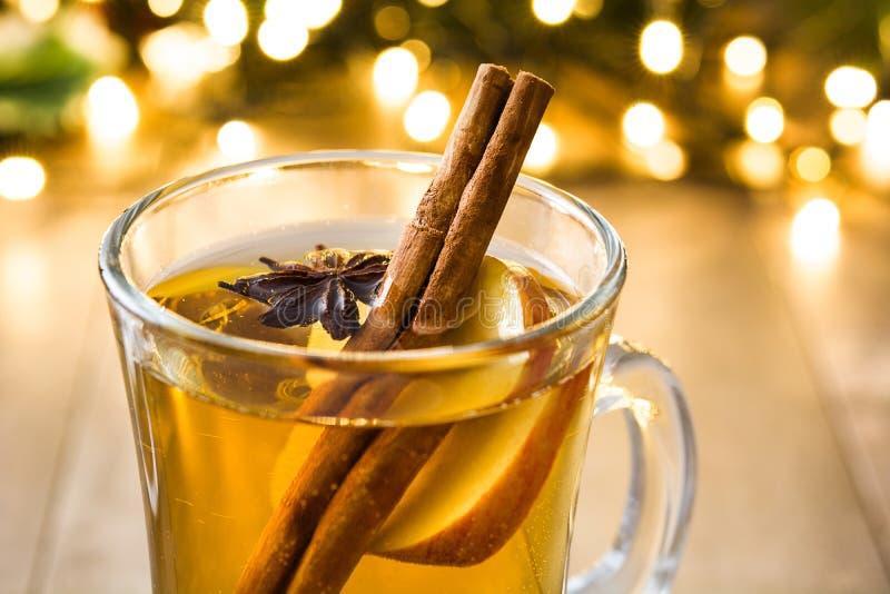 overwogen cider in glas, ornamenten en Kerstmislicht op hout royalty-vrije stock fotografie