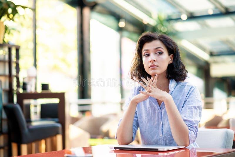Overwogen jonge vrouw in koffie met laptop royalty-vrije stock foto's