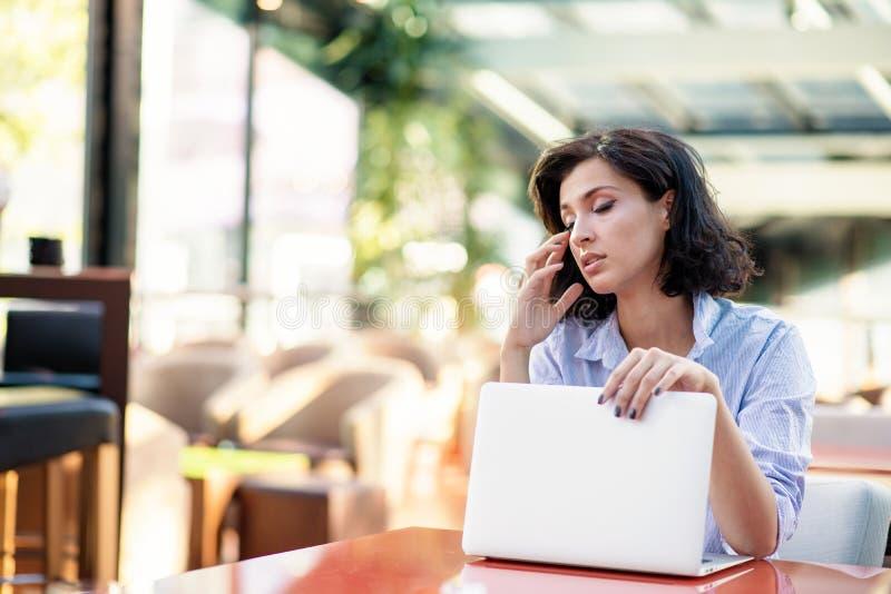 Overwogen jonge vrouw in koffie met laptop stock foto