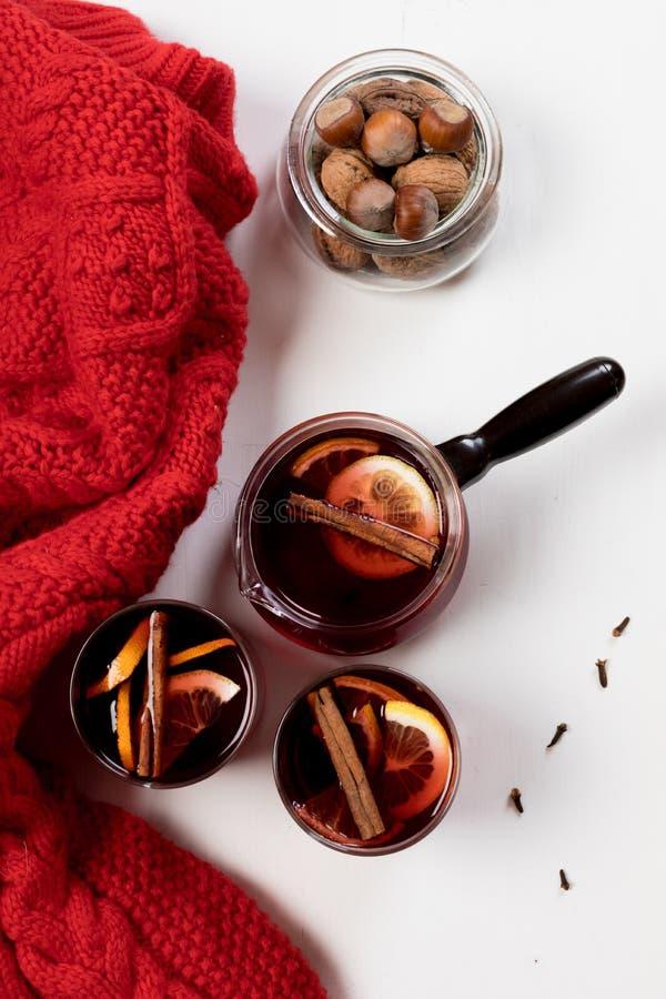 Overwogen wijn in glazen met sinaasappel en kruiden dichtbij rode sweater royalty-vrije stock afbeeldingen