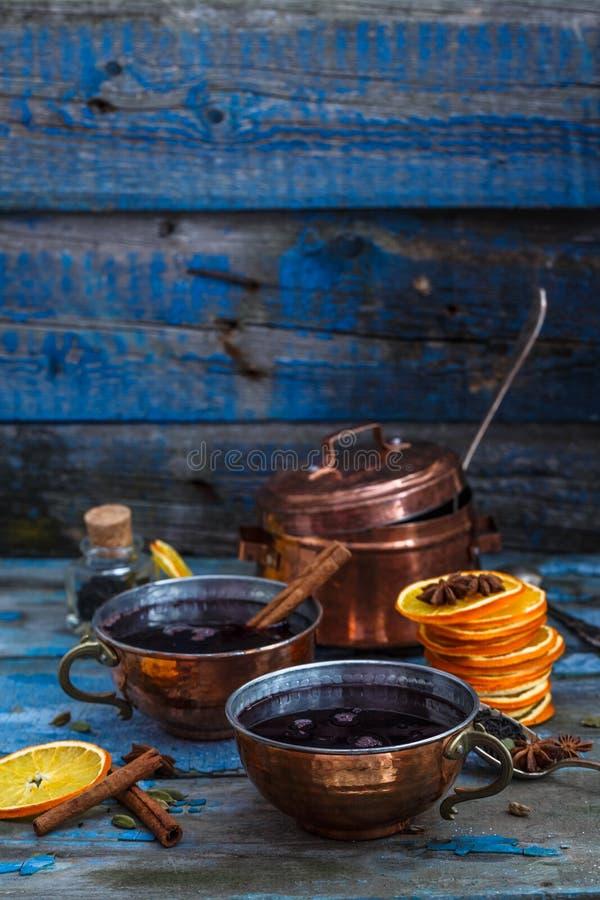 Overwogen wijn in koperkoppen met kruiden en citrusvruchten, exemplaarruimte stock afbeelding