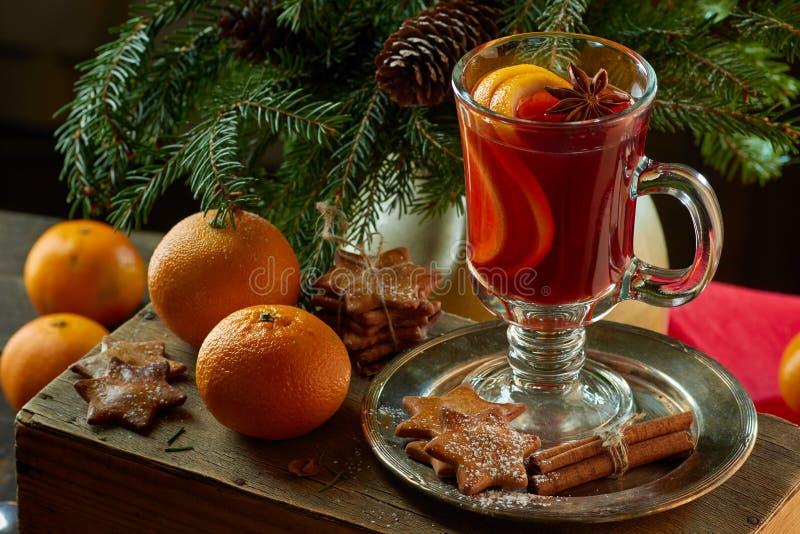 Overwogen wijn met pijpjes kaneel, mandarijn, gemberkoekjes en nette takken royalty-vrije stock foto