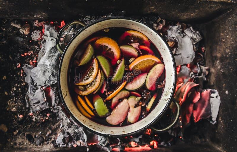 Overwogen wijnvoorbereiding rode wijn met kruiden, appel, sinaasappelen, kaneel, anijsplant, peper, notemuskaat royalty-vrije stock afbeeldingen