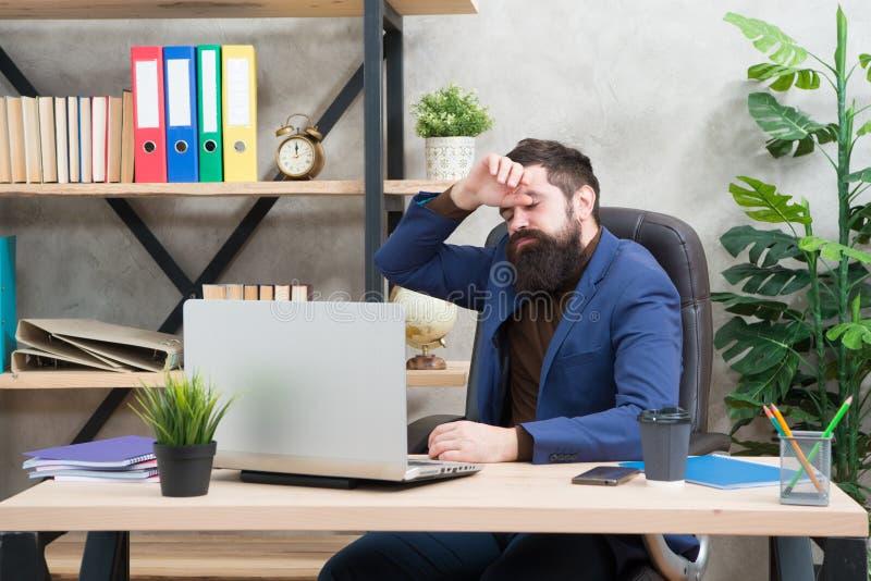 overwork Ha bisogno dell'aiuto uomo d'affari stanco in attrezzatura convenzionale Computer portatile e smartphone sicuri di uso d fotografie stock libere da diritti