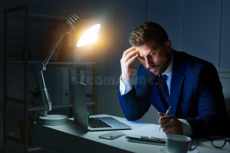 overwork Zakenman die met laptop en het schrijven rapport werken royalty-vrije stock foto