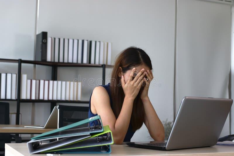 Overworked утомляло молодую азиатскую бизнес-леди с руками на депрессии чувства стороны в рабочем месте офиса стоковое изображение