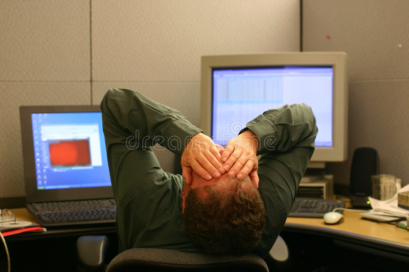 Overworked. Businessman sitting in front of computers covering his face with his hands stock photos