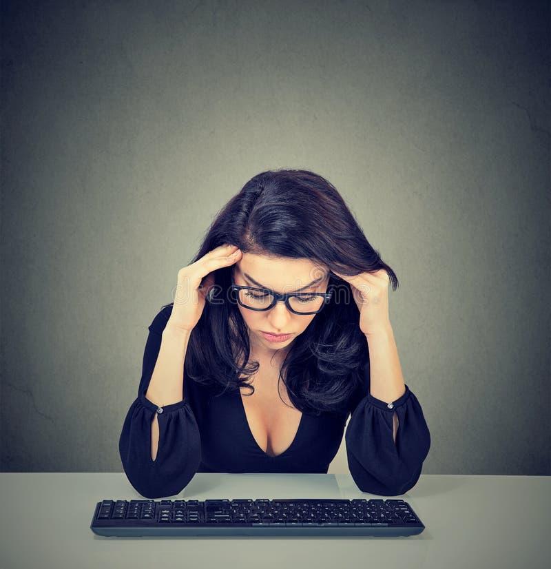 Overworked borrade kvinnasammanträde på skrivbordet framme av hennes dator som ner ser royaltyfri fotografi