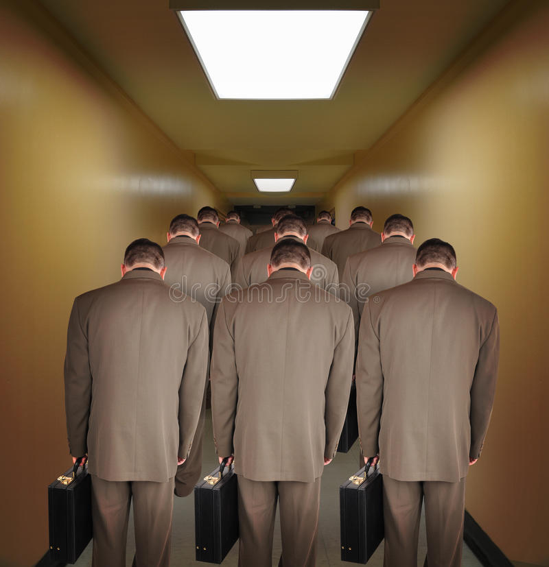 Overworked Business Men Walking down Hallway. Business men are walking down a hallway to do office work. The heads are down to symbolize pressure or royalty free stock photography