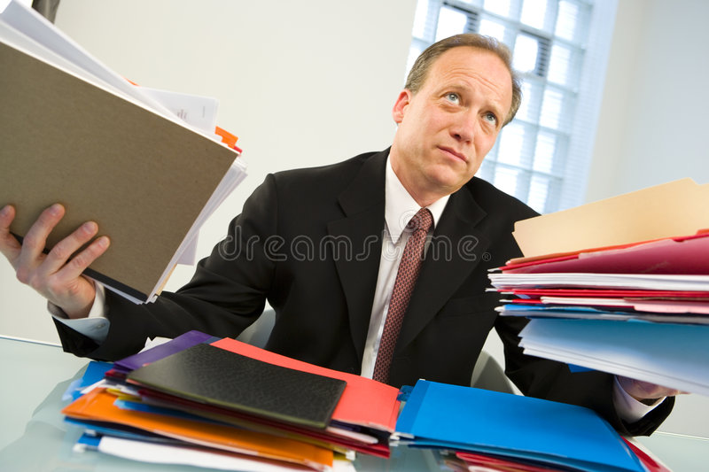 Overworked businessman. Portrait of overworked middle aged businessman surrounded by paperwork in office situation stock photos