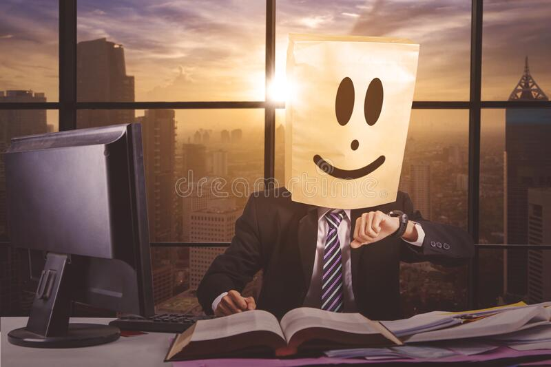 Overworked businessman look at his watch in office stock images