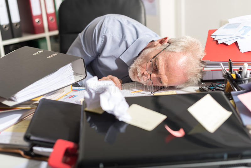 Overworked businessman sleeping on a messy desk. In office royalty free stock photos