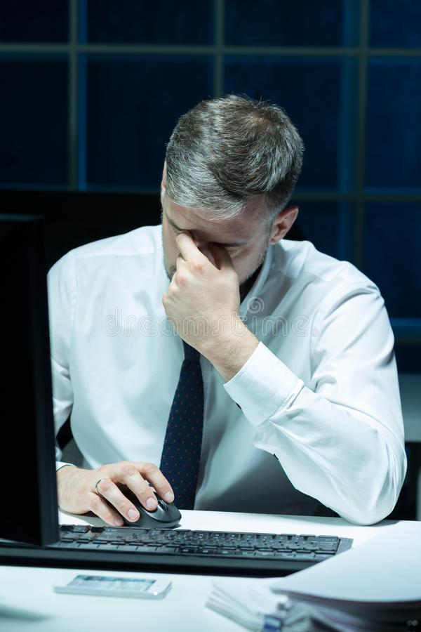 Overworked businessman working extra hours. Picture of overworked businessman working extra hours stock photos