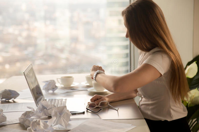 Overworked businesswoman looking at wristwatch, checking time to. Overworked businesswoman looking at wristwatch sitting at desk with laptop and crumpled paper stock photo