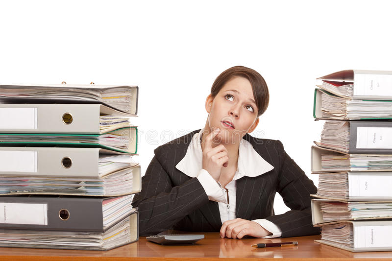 Overworked contemplative business woman in office. Between folder stacks. Isolated on white background stock photos