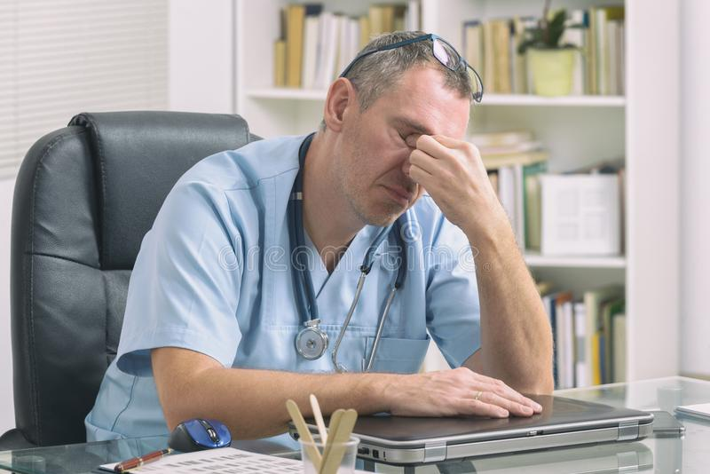 Overworked doctor in his office. Overworked doctor sitting in his office royalty free stock photo