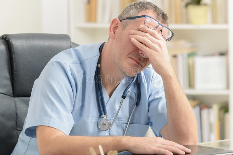 Overworked doctor in his office stock photography
