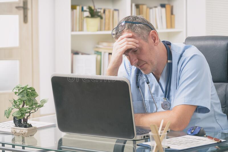 Overworked doctor in his office royalty free stock photos