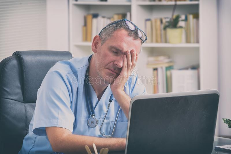 Overworked doctor in his office. Overworked doctor sitting in his office stock photo