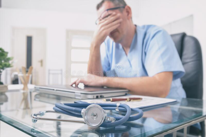 Overworked doctor in his office royalty free stock photography
