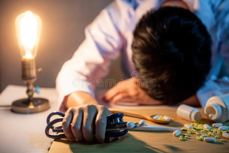 Overworked doctor sleeping on desk in hospital clinic. Overworked doctor sleeping with stethoscope in his hand on the desk in hospital clinic. Male practitioner stock image