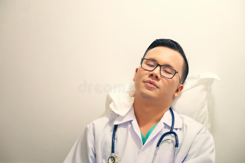 Overworked doctor sleeping with stethoscope in hospital clinic royalty free stock photos